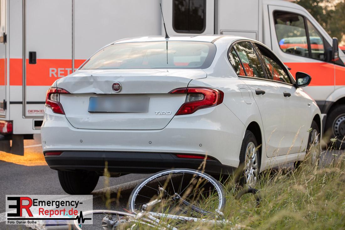 Fahrrad liegt hinter einem verbeulten Auto